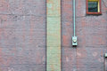 Window, meter box, and column against a purple painted brick wall Royalty Free Stock Photo