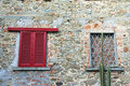A window with red shutters and a barred window Royalty Free Stock Photo