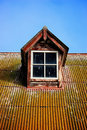 Window on a rusty corrugated iron roof Royalty Free Stock Photos