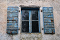 Window shutter chipped paint wooden with blue and textured wall of old house Stock Images
