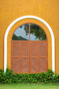 Window shutter of an orange house with grass Royalty Free Stock Image