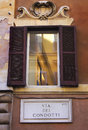 Window with shutters on the street Via del Condotti, Rome, Italy Royalty Free Stock Photo
