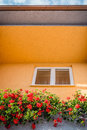 Window surrounded with yellow walls and flowers. Royalty Free Stock Photo