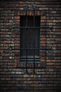 Window in a wall of bricks protected with metal bars Stock Photo