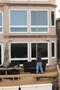 Window washer professional cleaning house windows with de ionized water using an extension pole Stock Photo