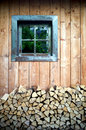 A window of wooden hut with cut woods in front Stock Photo