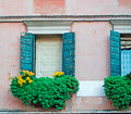Windows and flowers old with green shutters on the sill Royalty Free Stock Photo