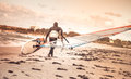Windsurfer with board on beach seaside back view sea windsurfing sport lifestyle concept Stock Photography