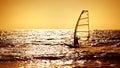 Windsurfer silhouette over sea sunset