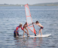 Windsurfing fun two little boys try to balance on board with child s sail next to them is male instructor Stock Image