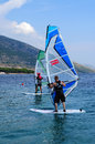 Windsurfing two men doing on mediterranean sea Royalty Free Stock Image