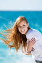 Windswept beautiful woman at the sea with her auburn hair flying in breeze smiling camera Stock Photos