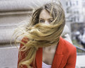 Windy day dressing in red a young woman is in a Stock Image