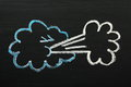 Windy weather symbol simple chalk drawing on a blackboard of a in the form of a cloud blowing wind Stock Photography