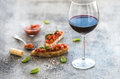 Wine appetizer set glass of red wine brushettas with fresh tomato and basil on over rustic grunge grey backdrop Stock Photography