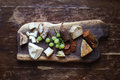 Wine appetizers set meat and cheese selection grapes bread on a rustic wooden board over a dark wood background top view Royalty Free Stock Photo