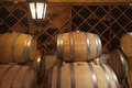 Wine barrels and bottles in dimly lit cellar Stock Photo