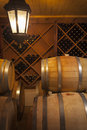 Wine barrels and bottles in dimly lit cellar Royalty Free Stock Image