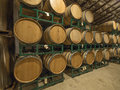Wine barrels in a cold warehouse stacked ready for drinking Stock Photos
