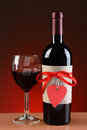 Wine bottle decorated for valentines day closeup of a a glass of is next to the the has a red ribbon and heart Stock Image