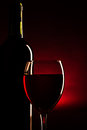 Wine bottle and glass silhouette over dark red Royalty Free Stock Photo