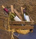 Wine bottles in basket with blank labels against a wall Stock Photos