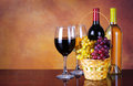 Wine bottles and glasses of wine basket of fresh grapes Royalty Free Stock Image