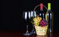 Wine bottles and glasses of wine over black background basket fresh grapes Stock Photos