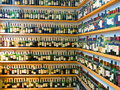 Wine bottles on shelves multiple rows of many different lined up two walls of that meet at a right angle Royalty Free Stock Photos