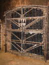 Wine in the cellar bottles closed old behind bars Royalty Free Stock Photography