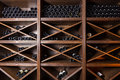 Wine cellar with bottles on wooden shelves Stock Photo