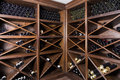 Wine cellar with bottles on wooden shelves Royalty Free Stock Photography