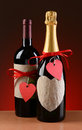 Wine and champagne bottles decorated of valentines for day the have red ribbons heart shaped tags vertical format on a Stock Photos