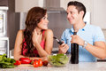 Wine and dinner with my partner happy brunette her boyfriend cooking about to open a bottle of Stock Photos