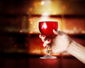 Wine glass being held in a womans hand of red young Stock Image