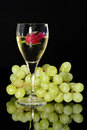 Wine glass and green grapes in the is a beautiful rose reflection on objects in vertical position Royalty Free Stock Photo