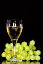Wine glass and green grapes reflection on objects in vertical position Royalty Free Stock Image