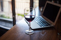 Wine glass with red wine and laptop computer. Royalty Free Stock Photo
