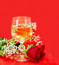 Wine in a glass with a rose white on red fabric Royalty Free Stock Photography