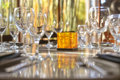 Wine glasses and glass buddha on shiny table with orange ornament Royalty Free Stock Photo