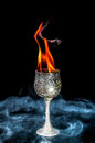 Wine goblet with fire flames with smoke on black background Stock Image