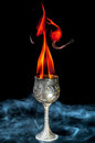 Wine goblet with fire flames with smoke on black background Stock Photos