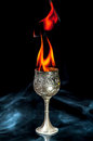 Wine goblet with fire flames with smoke on black background Stock Images