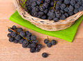 Wine grapes in basket merlot on wooden table Royalty Free Stock Photos