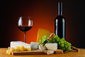 Wine grapes and cheese still life with glass bottle of red Royalty Free Stock Photo