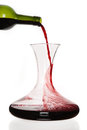 Wine pouring from the bottle into carafe isolated on white background Stock Photo