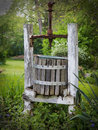 Wine press antique wooden left in garden surrounded by flowers Royalty Free Stock Images