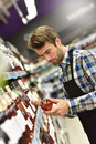 Wine specialist at work in supermarket putting bottle up winery section of Royalty Free Stock Images