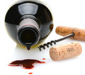 Wine spill closeup of a red bottle with a drip and in the foreground a cork screw and cork to one side on a white background Stock Photo