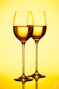Wine two glasses filed with white on yellow background studio shot Stock Photography